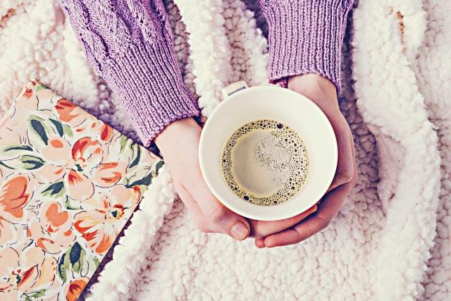 毛布の上でコーヒーを持つ手8