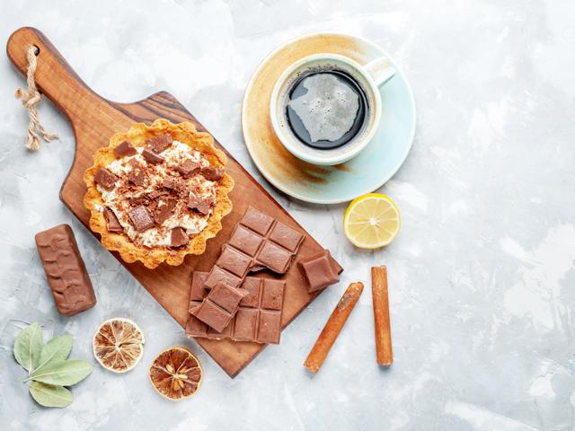 トップビュークリームの小さなケーキとチョコレートバーと軽い机の上のお茶甘いケーキクリームチョコレート