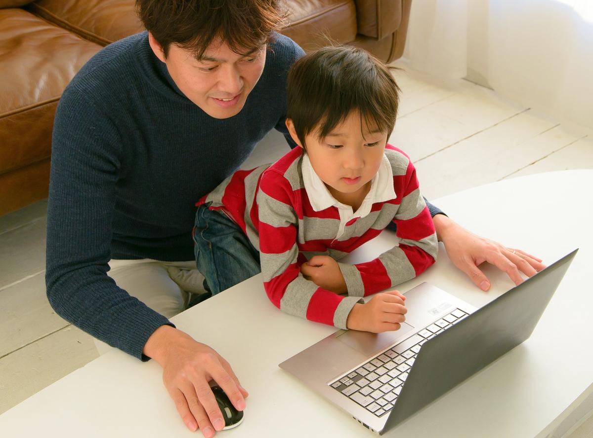 子どもにパソコンを教えるお父さん