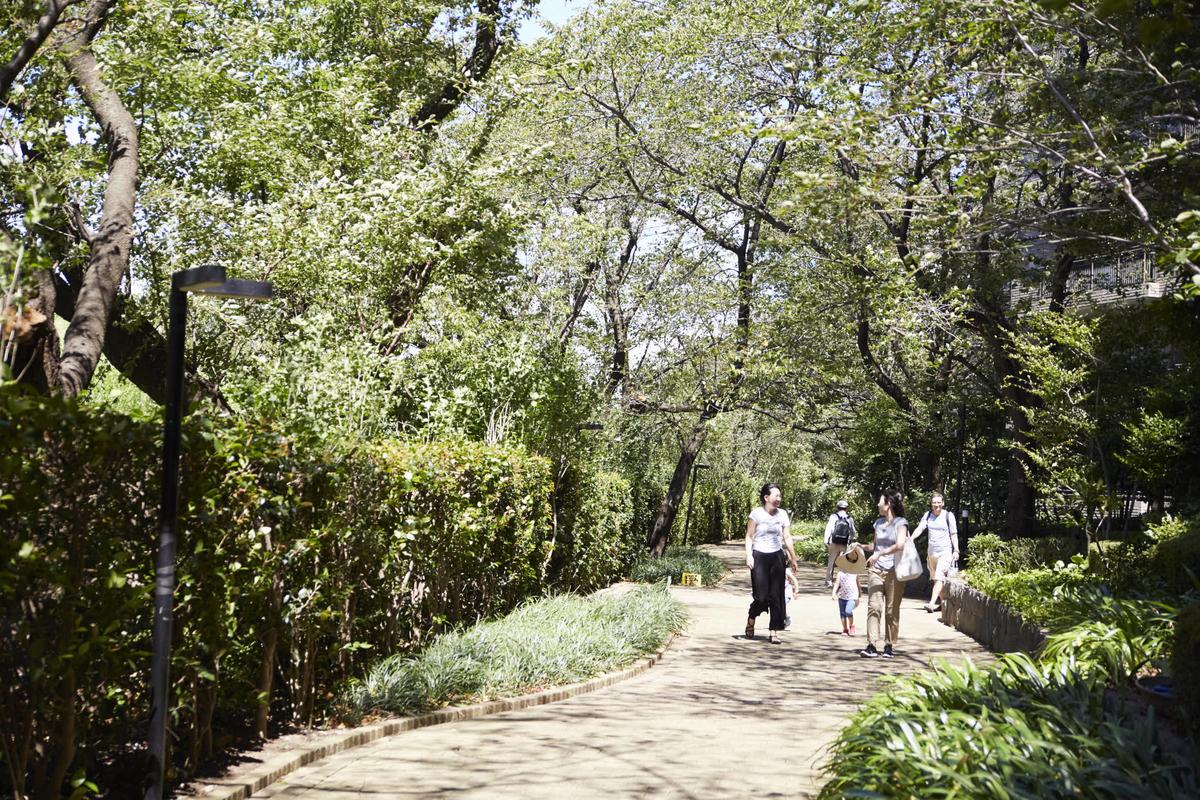パークハウス多摩川の緑豊かな敷地内を歩く家族