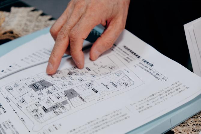阿倍野再開発の資料を指差す理事長