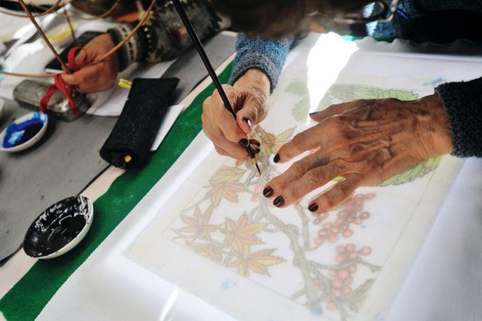 サンシティの染色クラブの活動の様子。図案を布地に写しているところ