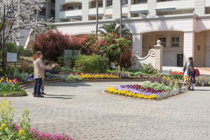 公園の花壇の前で記念撮影をする人