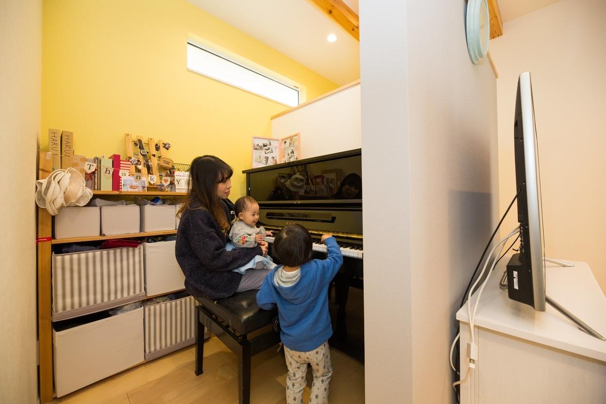 イエローの壁紙が印象的なピアノスペース/注文住宅実例
