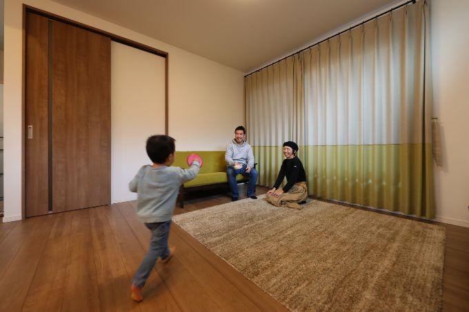 フルハイトの扉と天井のすぐ下からつるされたカーテンのあるリビング/注文住宅実例