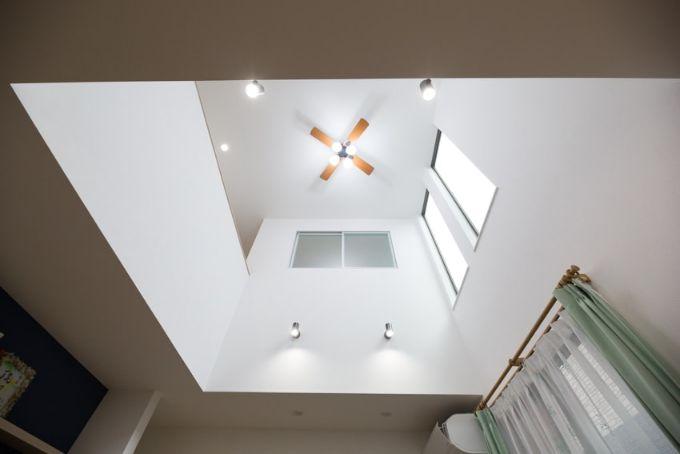 採光を考えた縦長の窓と吹抜けが開放的なリビング/注文住宅実例