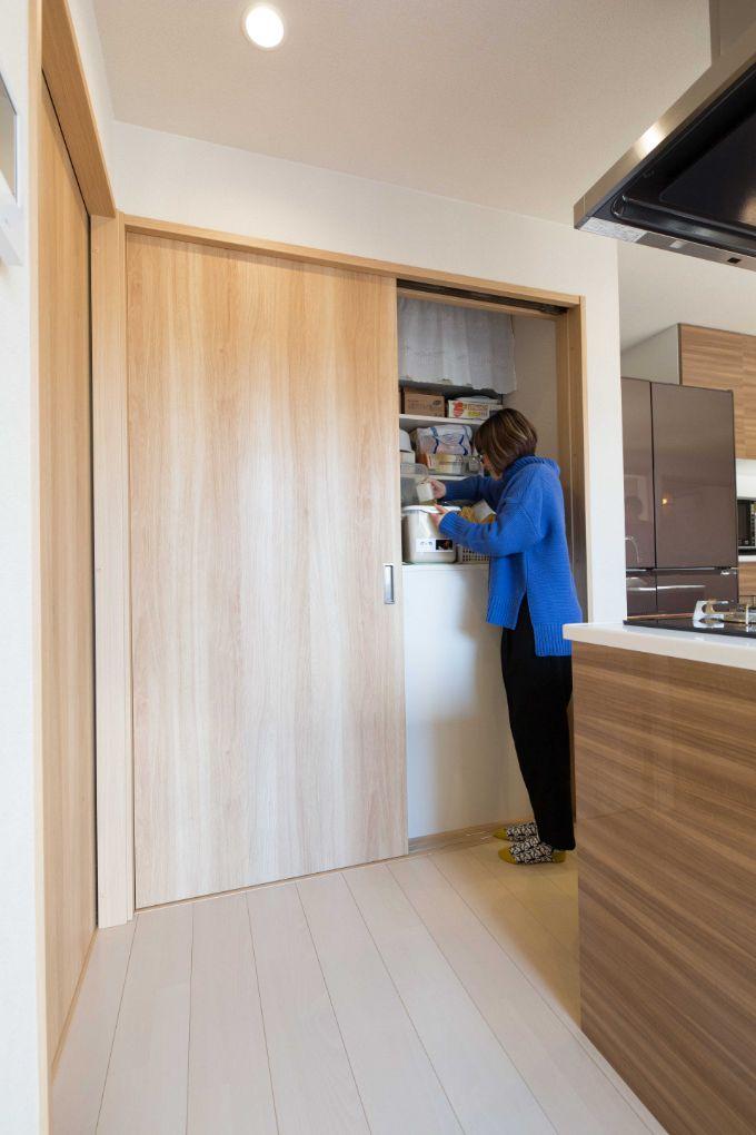 キッチンカウンターの背面の扉の右側を開けるとパントリーに/注文住宅実例