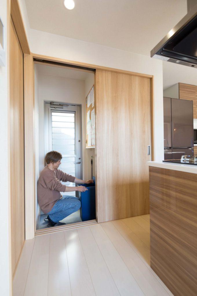 キッチンカウンターの背面の扉の左側を開けるとゴミ箱・勝手口につながる/注文住宅実例