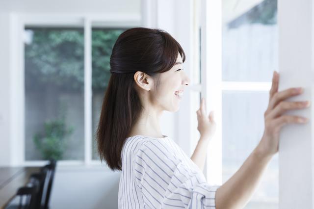 窓を開ける女性。吹抜けがある家では換気を心がけて