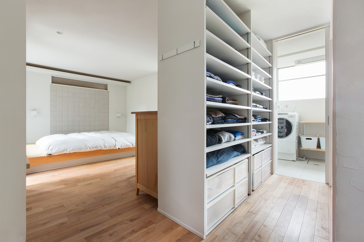 棚を使って空間をうまく区切った寝室とランドリースペースの写真