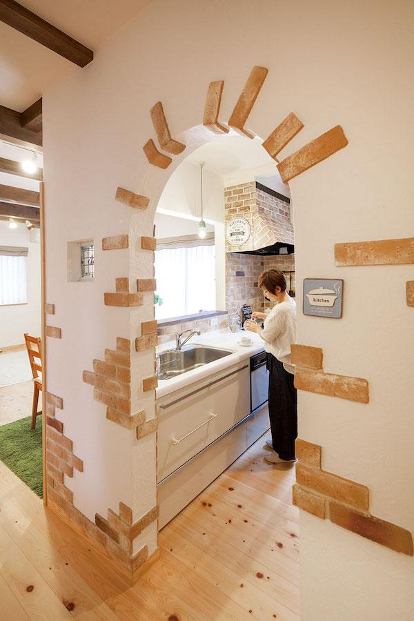 レンガやステンドグラスが埋め込まれたアール型のキッチン入口/注文住宅実例