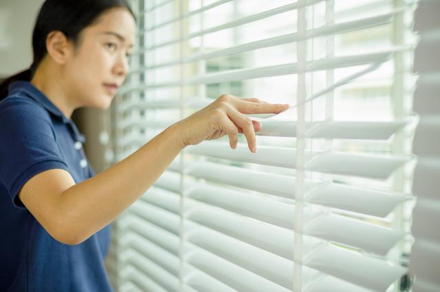 ブラインドのある窓の前に立つ女性