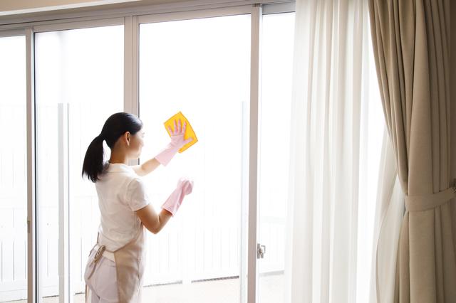 掃き出し窓の拭き掃除をする女性