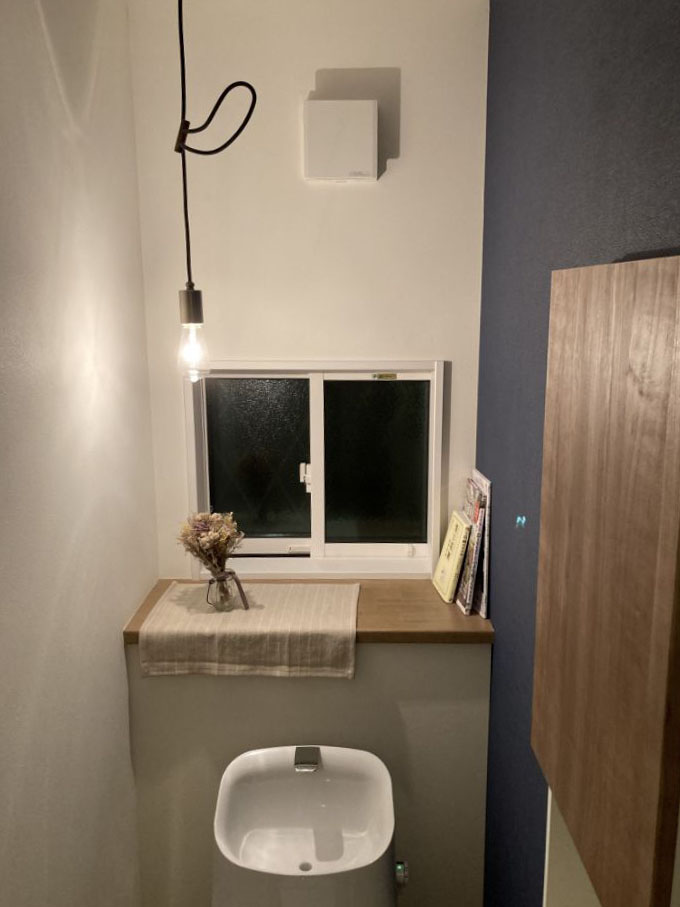 アクセントクロスと間接照明で雰囲気あるトイレ