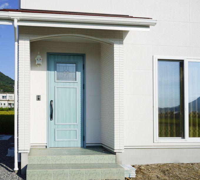 水色で目を引く玄関ドア/注文住宅実例