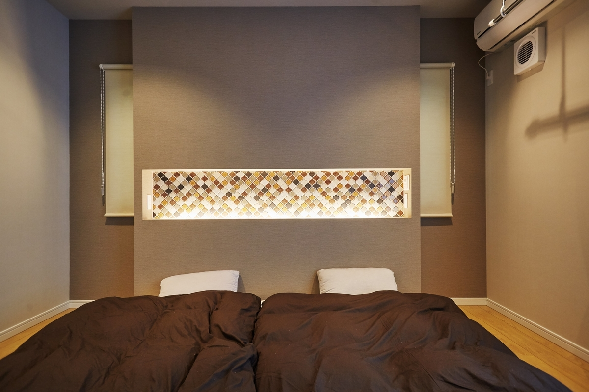 壁面に間接照明を取り付けた寝室