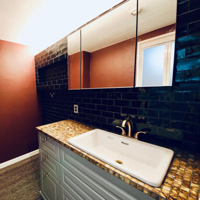 ブラックのカラータイルを使用した洗面所