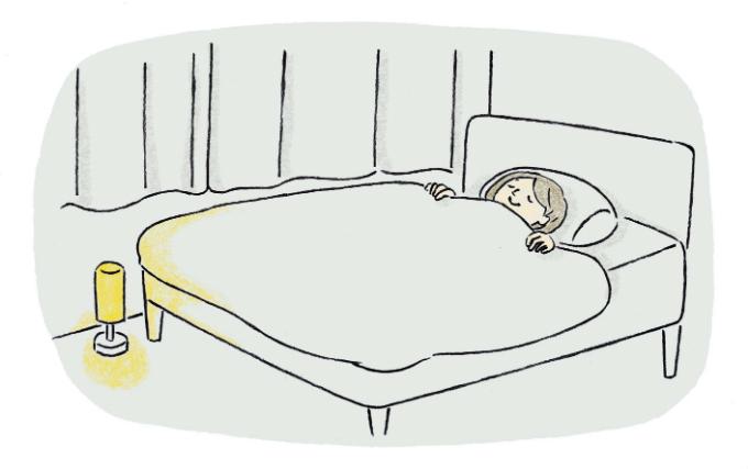 ベッドの足元に照明を置いているイラスト