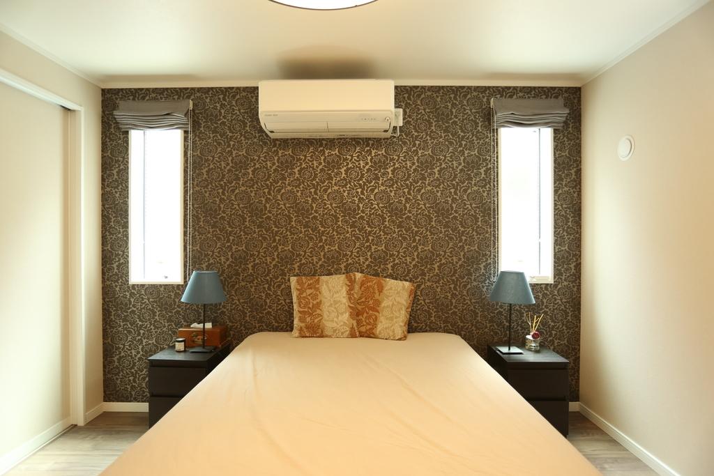 ベッドの両サイドにスタンドライトがある寝室