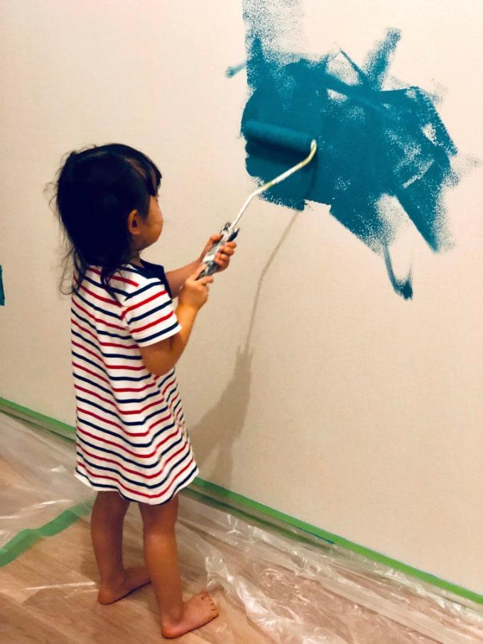 内壁に塗料を塗る子ども