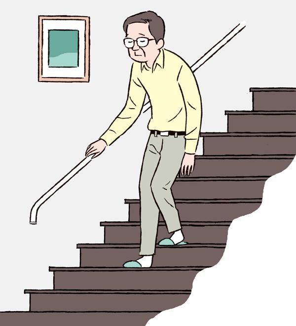 手すりを使って階段を下りる男性