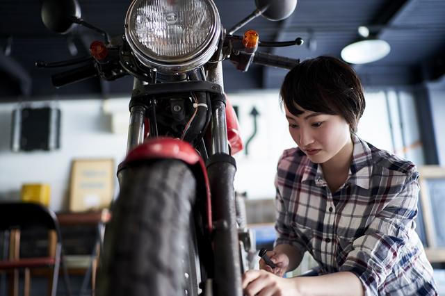 ガレージでバイクを触る女性