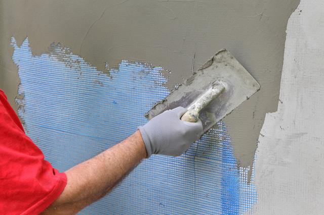 壁紙にモルタルを塗っている様子
