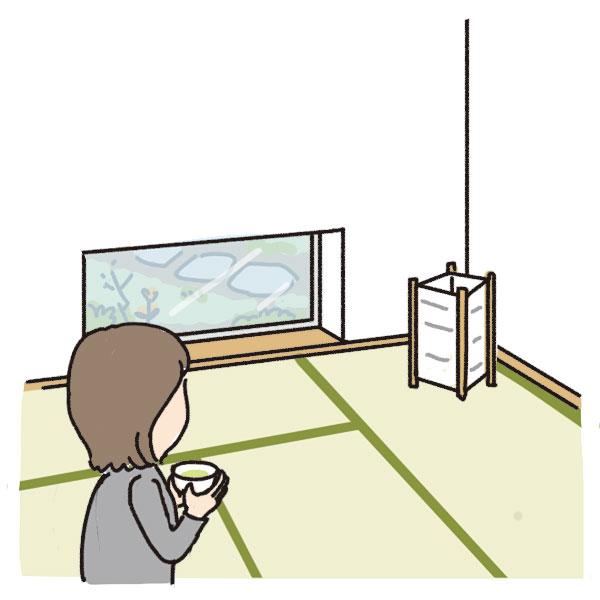 地窓のある和室でお茶を飲む女性