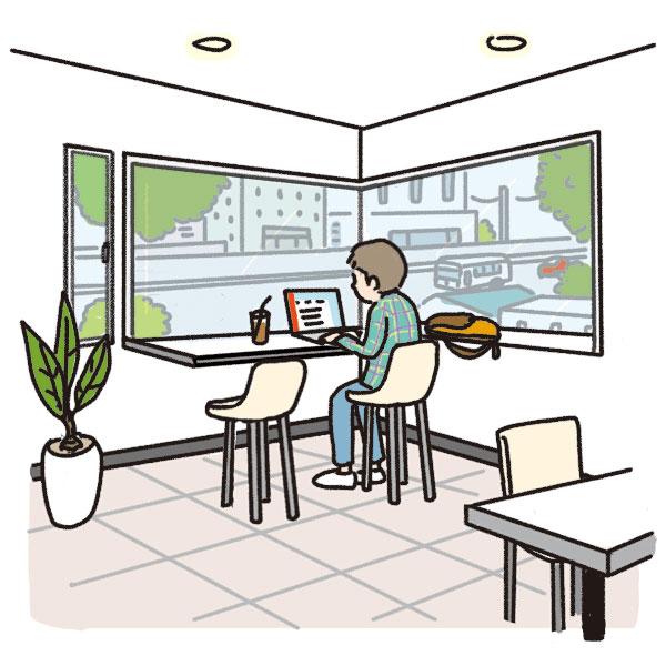 コーナー窓のある部屋でパソコンを使う男性