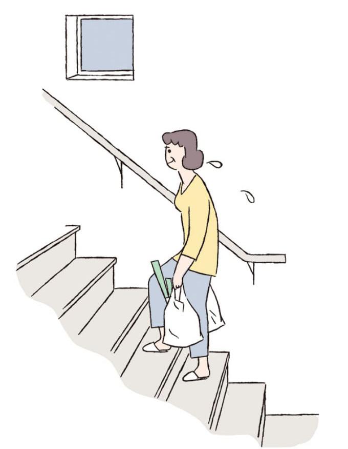 買い物の荷物をもって階段を登る女性