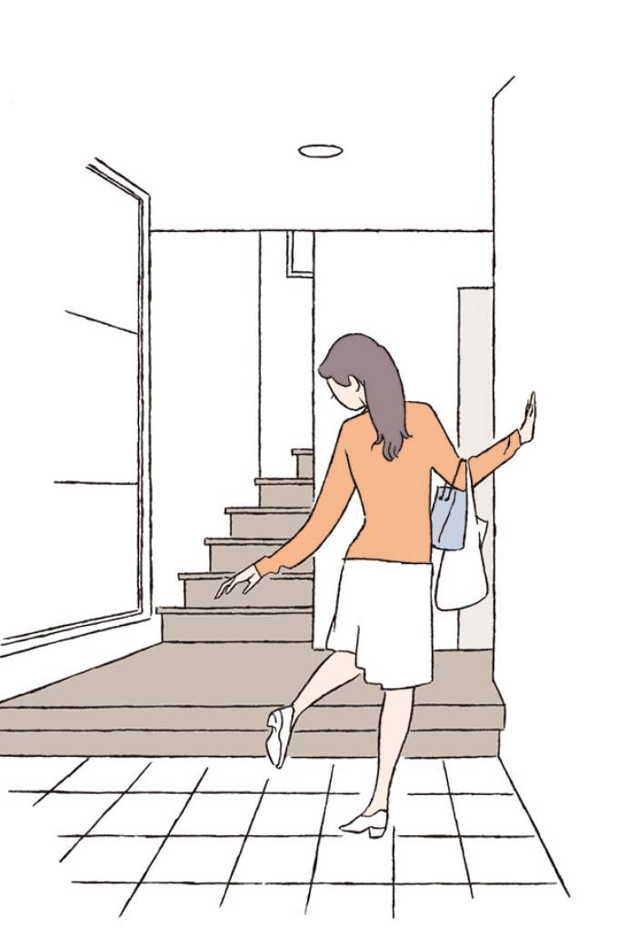 玄関で靴を脱ぐ女性
