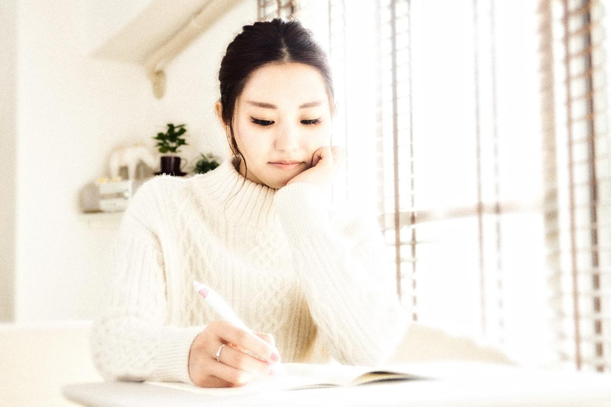 ノートに書く女性:Soseki21ブログ