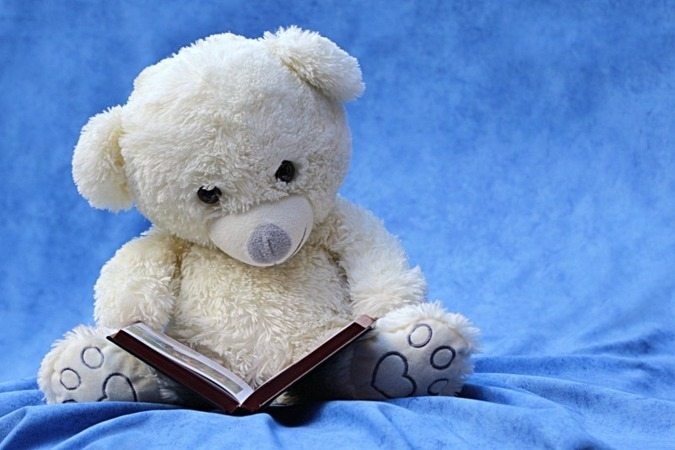 still-life-teddy-white-read-book-background-blue