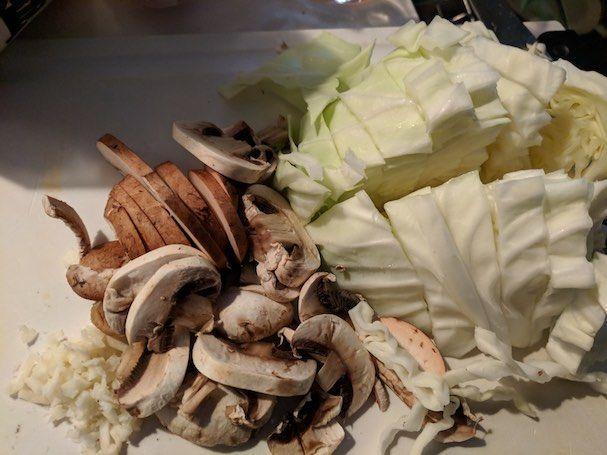キャベツ、マッシュルーム、にんにくを包丁で切った写真