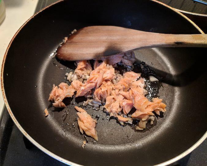鮭のほぐし身を追加して炒めている写真