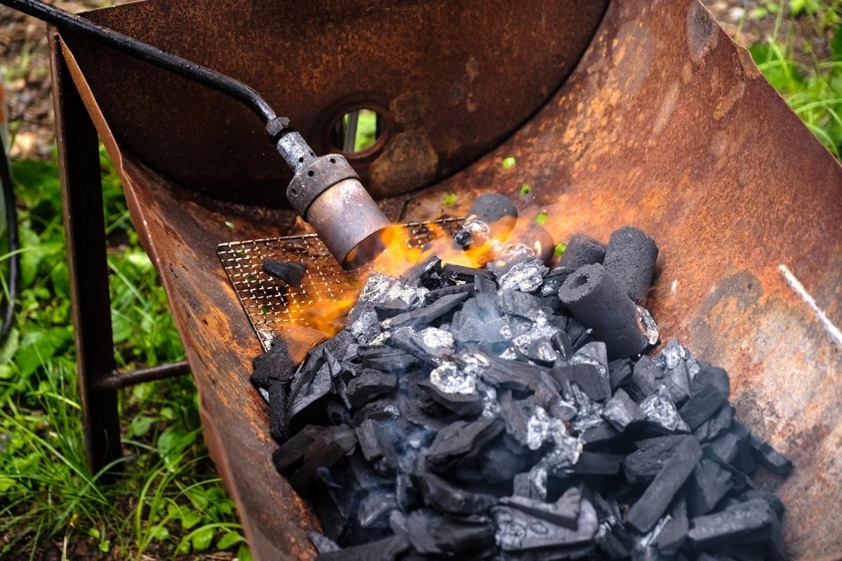 画像:トーチバーナーで炭に火をおこす