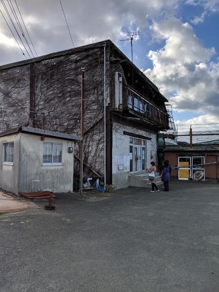 青島行きの欠航案内が掲示される建物前で外国人観光客が途方に暮れる