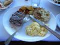 昼飯のステーキとスクランブルエッグとマフィン