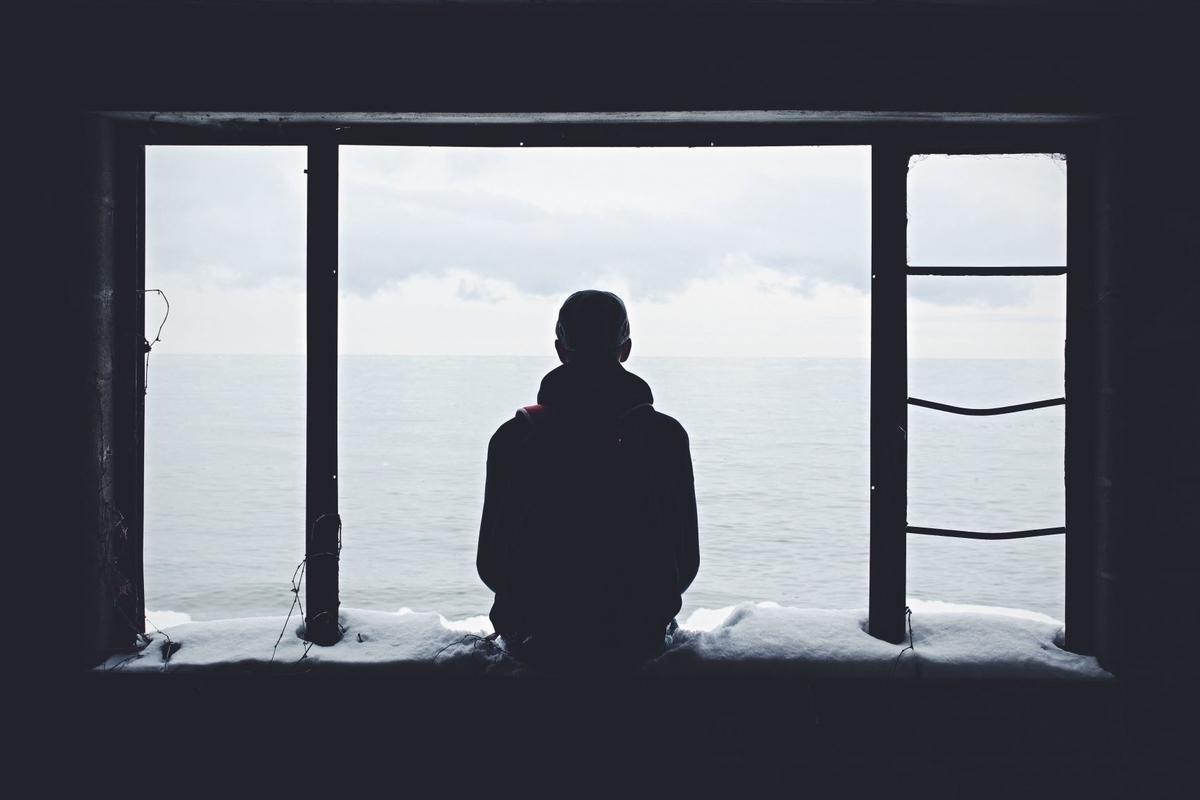 窓辺にたたずむ男性