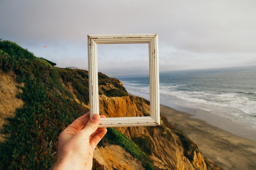 海に絵の枠をかざす人