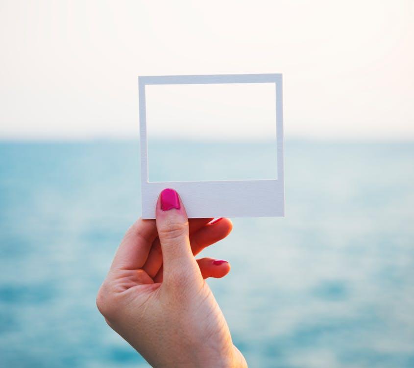 海を写真の枠で切り取る女性