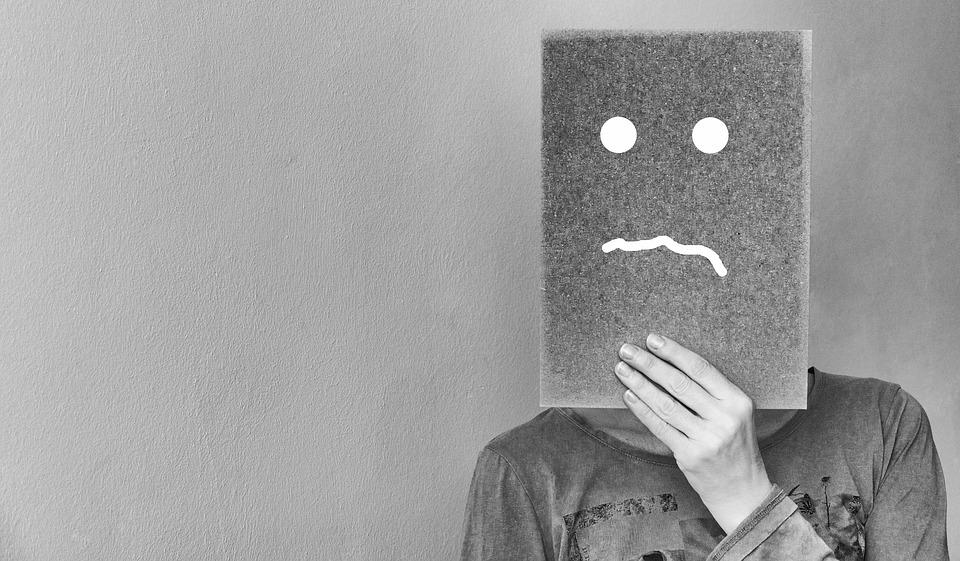 難しい顔をした紙で顔を隠す人