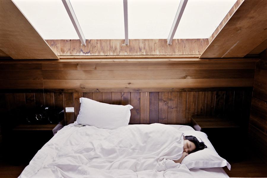 布団の中に入り寝ている女性