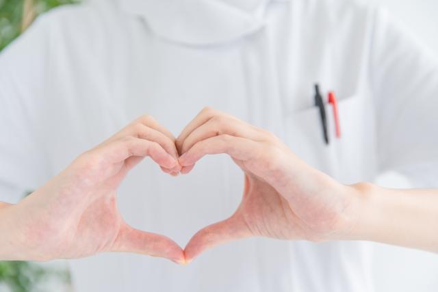 手でハートマークを作る看護師