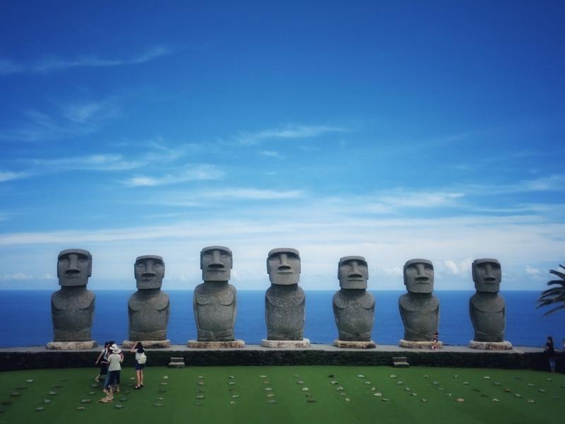 宮崎県日南市にあるサンメッセ日南にたたずむモアイ像の前で写真を撮る観光客