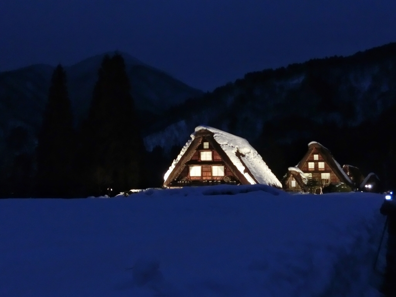 ライトアップされた白川郷のかやぶきの家。屋根には雪が積もっている