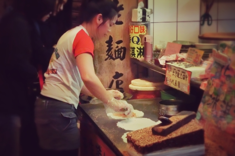 九份(きゅうふん)の屋台で客に売る飲食物を作っている女性