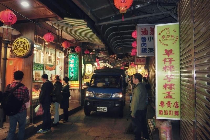 夜の九份(きゅうふん)の狭い路地を走る車