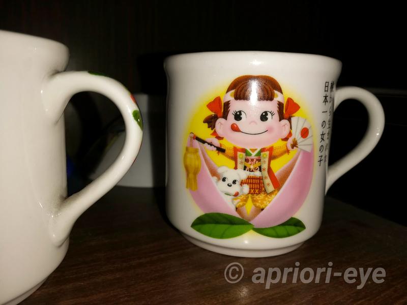 桃太郎からくり博物館に展示されているペコちゃんのマグカップ。桃からペコちゃんが生まれているところが描かれている