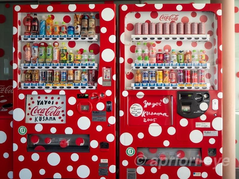 赤い背景に白い水玉模様が描かれた自動販売機